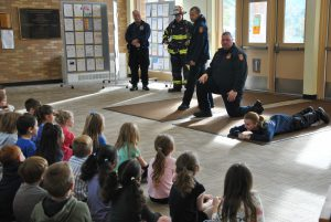 "A group of firefighters addresses a student assembly in the school lobby. One firefighter is demonstrating ""stop, drop & roll"" exercises."