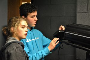 Two students operating stage lights