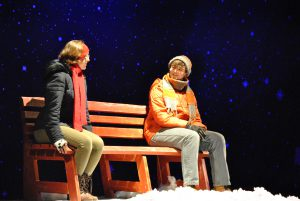 Two students dressed for the cold sit on a bench. There's a starry sky behind them and snow on the foreground.