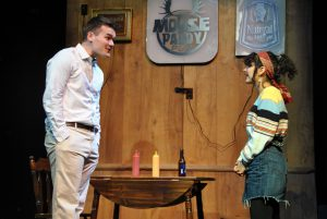 Two actors on stage playing a bar scene