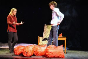 Two students on stage playing a couple having an argument. There are several large red bags on the floor and a tiny red bag on a side table.