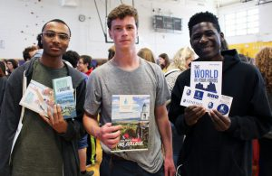 Three students with college materials