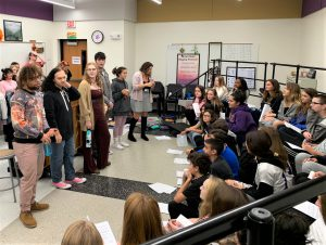 A group of high school students presents to a class of younger students in a music room