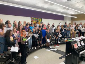 High school and middle school students singing together in a music room