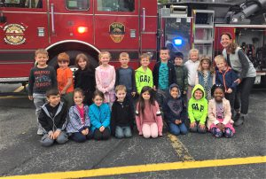 A class and their teacher pose in front of a fire engine.