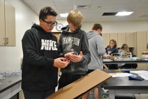 Two students focus on a lab - one student pushes a car down a cardboard ramp while the other holds a stopwatch
