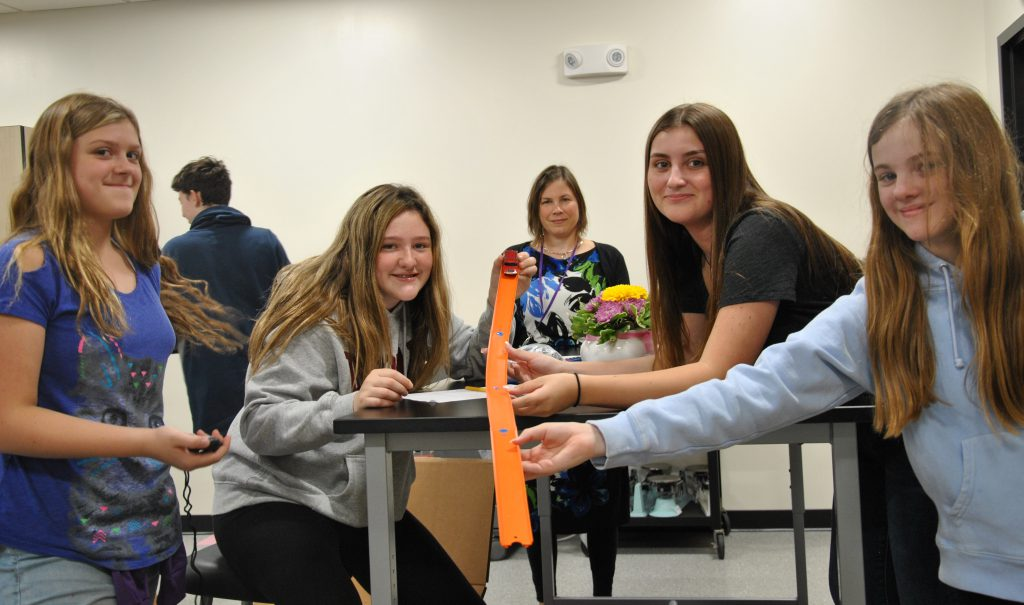 Four students and one teacher look up from a table to pose. they are holding a car ramp.