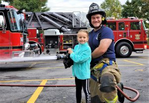 A firefighter helps a student holding a jetting fire hose