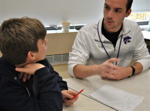 Teacher talking with student and drawing on a sheet of paper