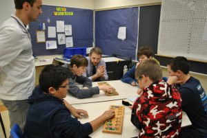 Students playing mancala while two teacher observe