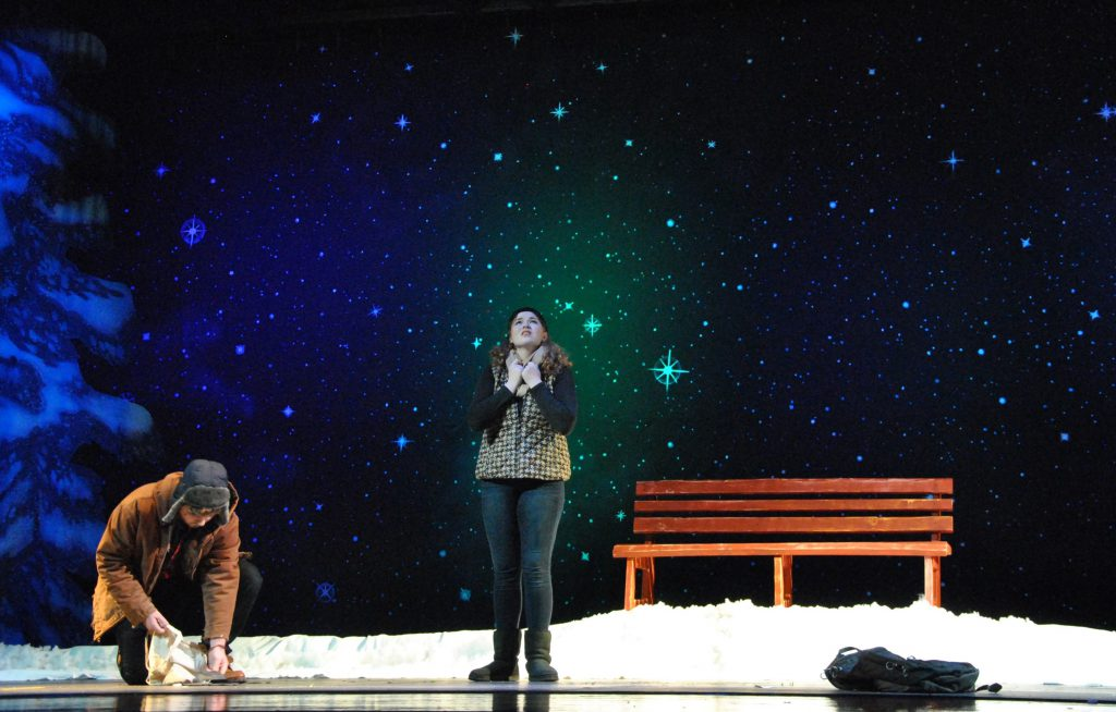 Two Actors performing on a stage. Set is a starry night, and a bench on a mound of snow. One actor is looking up at the sky. The other is picking up rocks off the floor and placing them in a bag.