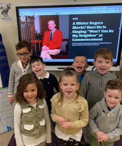 kindergarteners standing in front of a Mr. Rogers photo