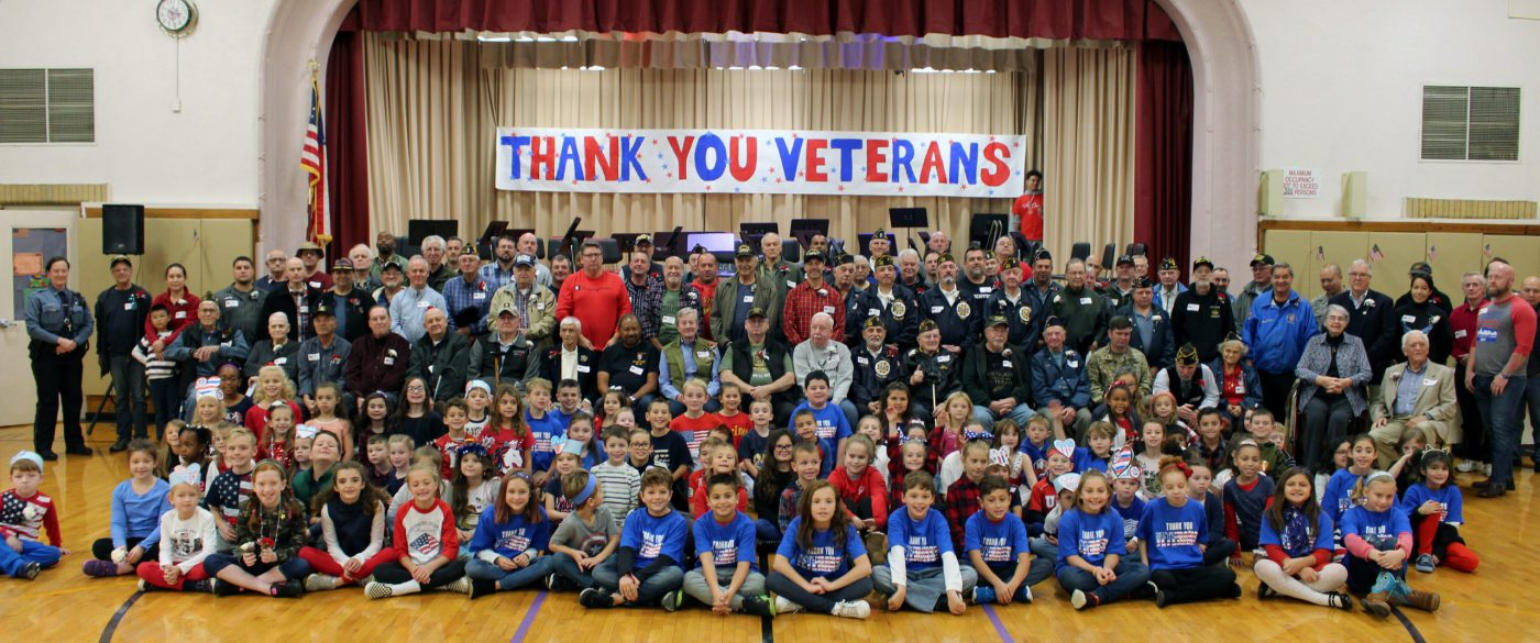 Students, school staff and community members pose for a group photo after a ceremony honoring US Veterans.