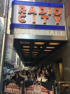 Groupof students waving outside of Radio City Music Hall