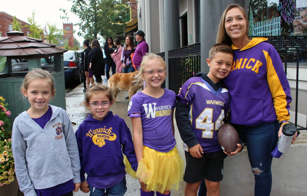 Four students and an adult pose for a photo during the Homecoming parade. They are all wearing the district colors and logos