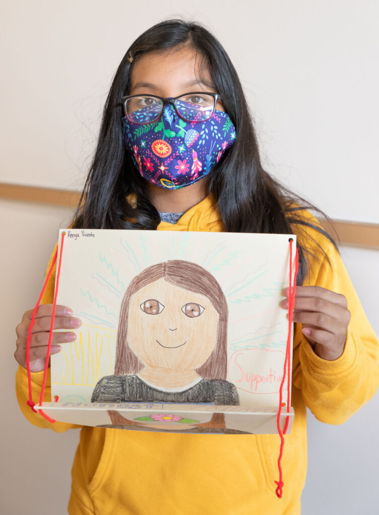 Sixth grader Kenya Vicente holds up a self portrait she did as part of a class project at Warwick Valley Middle School on Sept. 21, 2020.