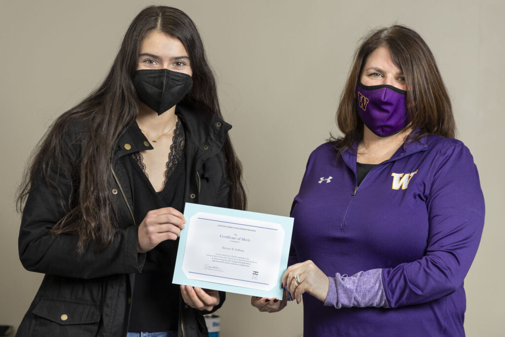 Warwick Valley High School Principal Marguerite Fusco presents senior Simone Sullivan with a Certificate of Merit for being named a finalist in the National Merit Scholarship program on Feb. 12, 2021.